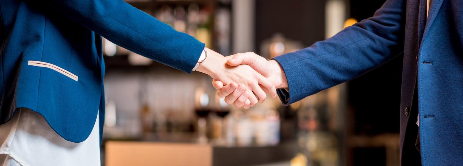 Handshake between business partners at cafe