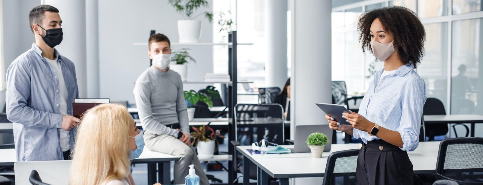 Team at work talking wearing masks.
